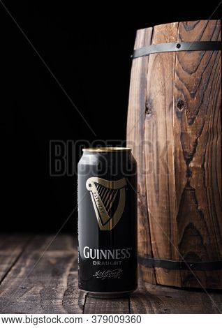 London, Uk - April 27, 2018: Aluminium Can Of Guinness Draught Stout Beer  Next To Old Wooden Barrel