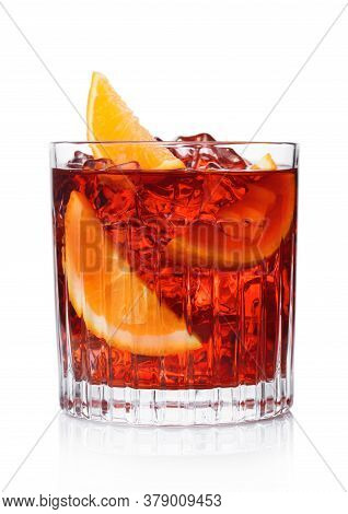 Negroni Cocktail In Crystal Glass With Ice Cubes And Orange Slices On White Background