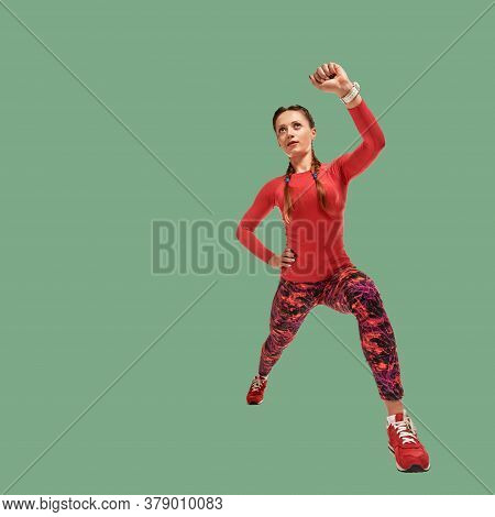 Strong Fit Healthy Woman Squatting With Raised Hand On Green Background