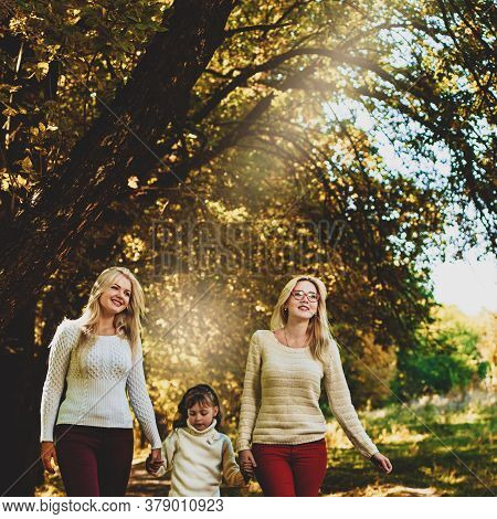 Little Girl With Two Elder Sisters Walking Outdoor In Autumn Forest