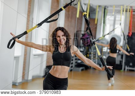 Fit Woman With Slim Body Doing Suspension Training With Fitness Straps