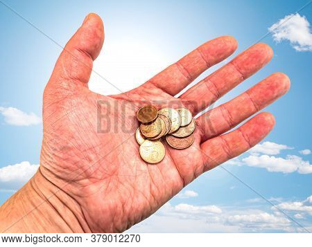 Hand With Money Coins On A Background Of Blue Sky.