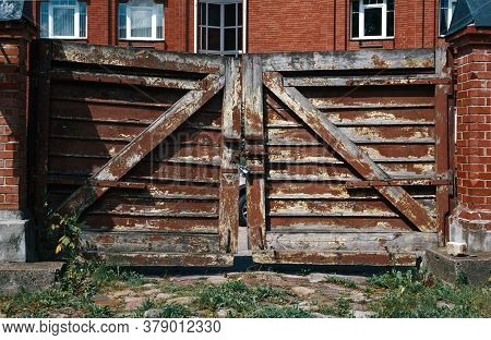 Shabby Wooden Gates With A Lock Near Red Brick Country House