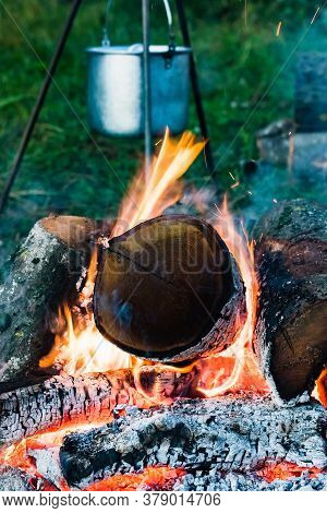 Camping Bowler Hat Hangs Over The Fire On A Tripod