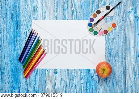Blank sheet, paints and paint brushes on blue wooden background. Top view, copy space. School accessories for children's education and development. Art lesson or drawing