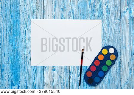 Blank sheet, paints and paint brushe on blue wooden background. Top view, copy space. School accessories for children's education and development. Art lesson or drawing