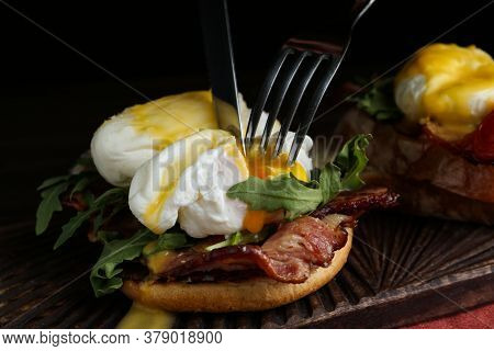 Cutting Tasty Egg Benedict On Wooden Board, Closeup