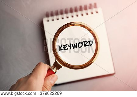 Woman Looking At Word Keyword Written In Notebook Through Magnifying Glass, Closeup