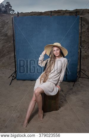 Beauty Portrait Outdoors On Sand In Front Of Blue Background, Pretty Female In Hat. Attractive Cauca