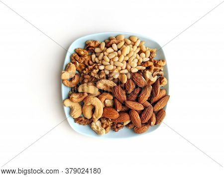 Small Plate Of Assorted Nuts With Walnuts, Cashew, Almonds And Pine Nuts, On A Light Blue Coffee Coa