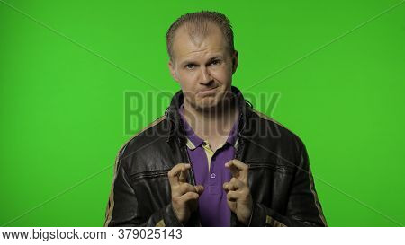 Rocker Man In Brown Leather Jacket Full Of Hope Crossing His Fingers Showing Good Luck Gesture, Wish
