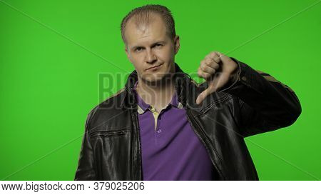 Dislike To You. Rocker Man In Brown Leather Jacket Pointing To Camera And Showing Thumbs Down, Looki