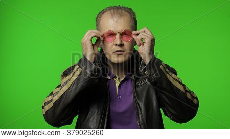 Cool Brutal Rocker Man In Brown Leather Jacket Puts On Pink Sunglasses, Looks At The Camera And Smil
