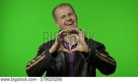 Nice Handsome Brutal Rocker Man Taking Out Heart Gesture From His Leather Jacket And Demonstrating A