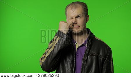 Funny Stupid Rocker Man In Jacket Picking Nose With Silly Brainless Humorous Expression, Removing Bo