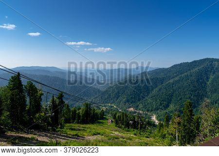 Altai, Russia - July 20, 2020. Cable Car Chair Lift In The Mountains. Climbing The Mountain On A Lif