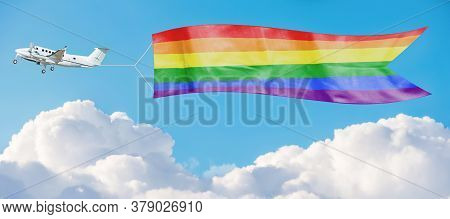 Rainbow Lgbt Flag Among The Clouds Tug By Airplane In The Sky.  Support And Tolerance For Sexual Min