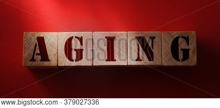 Aging - Word From Wooden Blocks With Letters, On Red Background. Growing Old Senescence Aging Health