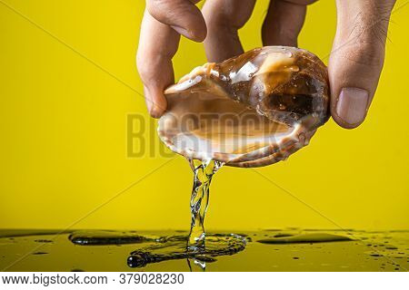 Hand Pours Water From A Seashell On A Yellow Background. Marine Inhabitant. Creative Photo Of A Seas