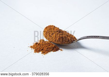 Red Ground Pepper On A White Background. A Spoonful Of Red Ground Pepper. Spicy Seasoning