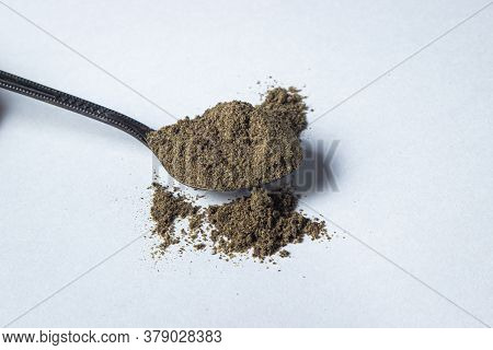 Black Ground Pepper On A White Background. A Spoonful Of Ground Black Pepper. Spicy Seasoning