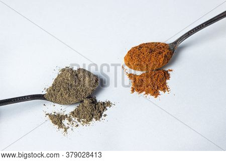 Red And Black Ground Pepper On A White Background. The Spoon With Black Pepper Lies Next To The Spoo