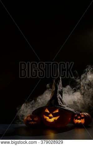 Vertical Halloween Card. Witch Hat On A Pumpkin With Carved Creepy Grimaces On A Black Background In