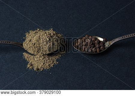 Black Ground Pepper And Peppercorns On A Black Background. A Spoon With Black Pepper Lies Next To A