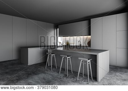 Corner Of Stylish Kitchen With Gray And Brick Walls, Concrete Floor, Gray Cupboards And Bar With Woo