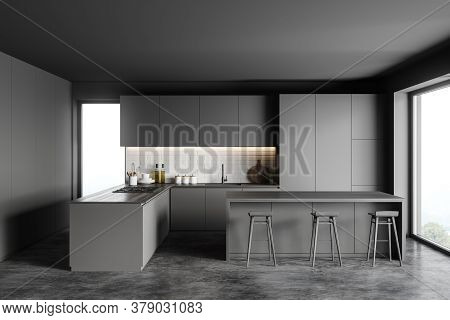 Interior Of Stylish Kitchen With Gray And Brick Walls, Concrete Floor, Gray Cupboards And Bar With S