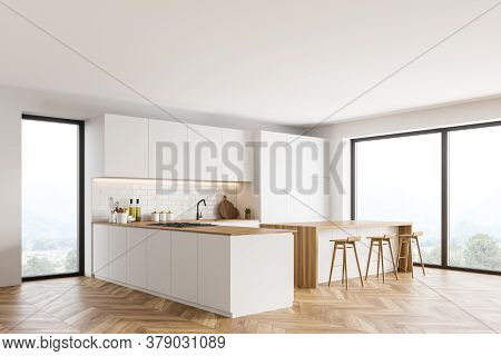 Corner Of Modern Kitchen With White And Brick Walls, Wooden Floor, White Cupboards And Bar With Stoo