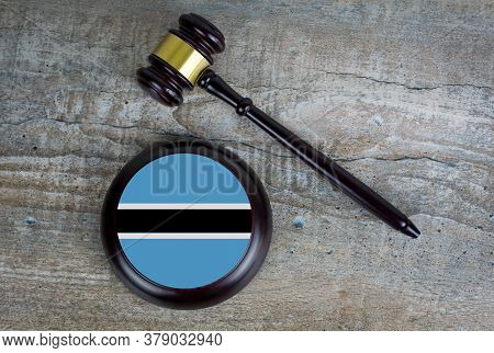 Wooden Judgement Or Auction Mallet With Of Botswana Flag. Conceptual Image.