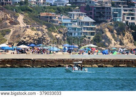 July 30, 2020 In Newport Beach, Ca:  Boat Riding Into The Harbor With Beachgoers Sunbathing On The S