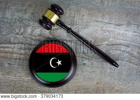 Wooden Judgement Or Auction Mallet With Of Libya Flag. Conceptual Image.