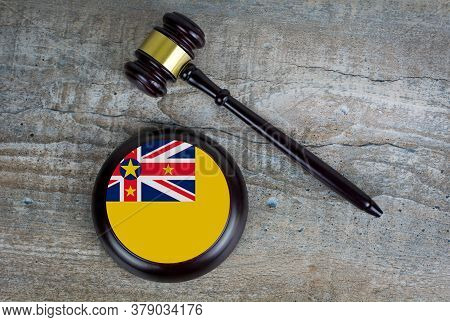 Wooden Judgement Or Auction Mallet With Of Niue Flag. Conceptual Image.