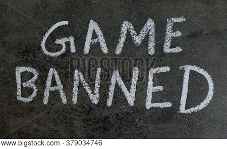 Game Banned Phrase Written On Blackboard With White Chalk