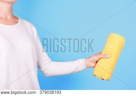 Hand With Folded Yellow Towel. Isolated On Blue Background.