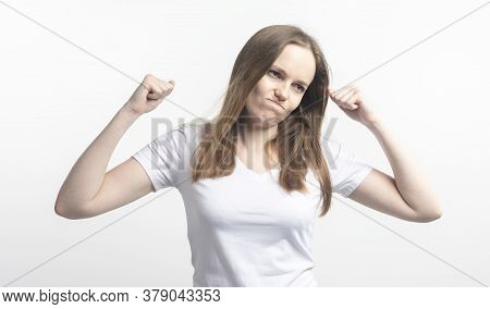 Disappointed Young Woman Raises Her Hands In Frustration On A White Background In The Studio