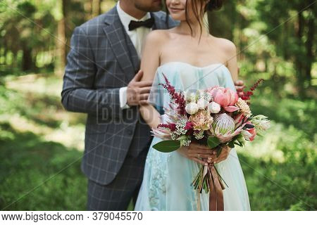 Bride And Groom At The Wedding Day Walking Outdoors In Summer Nature. The Bridal Couple, Happy Newly
