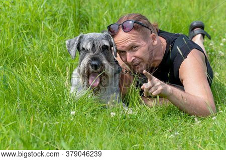 Senior Man Playing With His Dog Lying On The Grass In The Park.