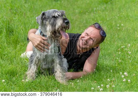 Senior Man Hugging His Dog Lying On The Grass In The Park.