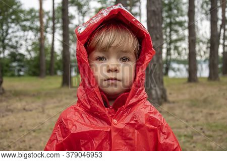 A Little Girl In A Red Raincoat With A Hood In A Tourist Camp Against The Background Of The Forest.