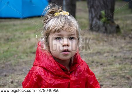 A Little Girl In A Red Raincoat With A Hood In The Forest At A Tourist Rally With Tents.outdoor Recr