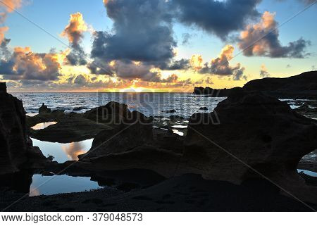 Unusual Forms Of Volcanic Cliffs Of Lava On The Rocky Shore. Beautiful Sunset Over The Atlantic Ocea