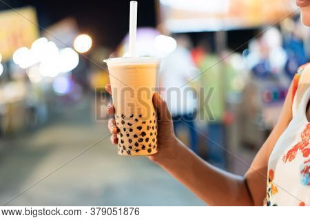 Asian woman holding the famous taiwanese bubble milk tea at night marketplace