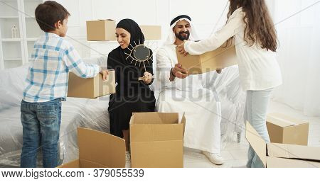 Arabian Married Couple In Traditional Middle Eastern Clothes Siting On Couch And Unpacking Carton Ho