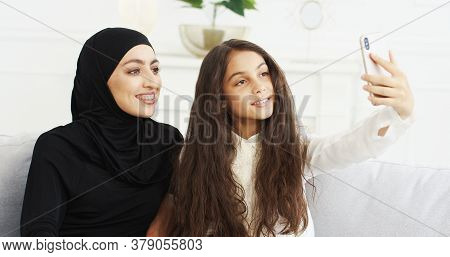 Beautiful Teen Small Girl And Young Arabian Mother In Hijab Sitting On Couch And Taking Selfie Photo