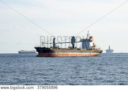 Old Commercial Cargo Ship With Heavy Cranes Anchors In The Sea.