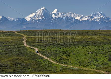 Amazing View With A Car On A Winding Dirt Road Going Along The Slope Of The Mountain Among The Thick