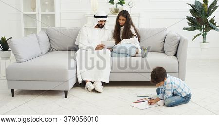 Arabian Father In White Kandura Playing With Small Kids, Daughter And Son In Living Room. Muslim Dad